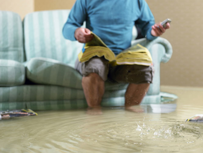 HMS-Plumbing-Man-in-a-Flooded-Living-Room