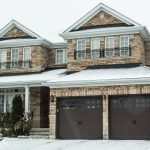 A big house with snow on the roof and the front yard.